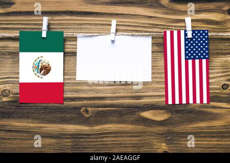 Hanging flags of Mexico and United States attached to rope with clothes pins with copy space on white note paper on wooden background.Diplomatic relat - Stock Photo