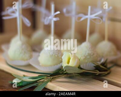 Many white sweet rolls and a white rose in front of them - Stock Photo