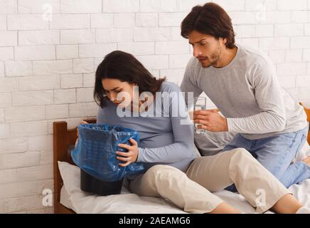 Pregnant woman suffering from morning sickness, vomiting to garbage can - Stock Photo