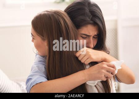 Girl Crying Hugging Her Compassionate Friend Sitting On Couch Indoor - Stock Photo