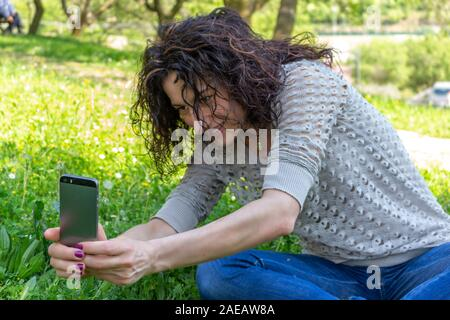 Young woman taking a photograph at a flower with iphone - Stock Photo