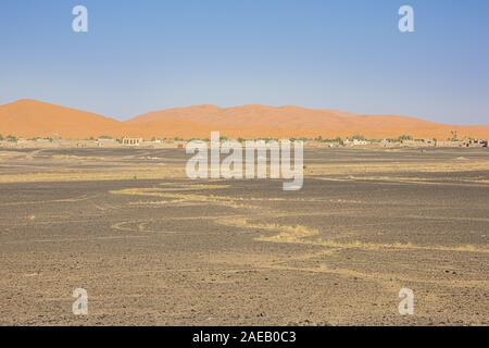 View of the sand dunes of Erg Chebbi with Merzuga in the foreground - Stock Photo