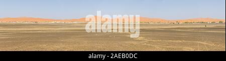 Panorama of the sand dunes of Erg Chebbi with Merzuga in the foreground - Stock Photo