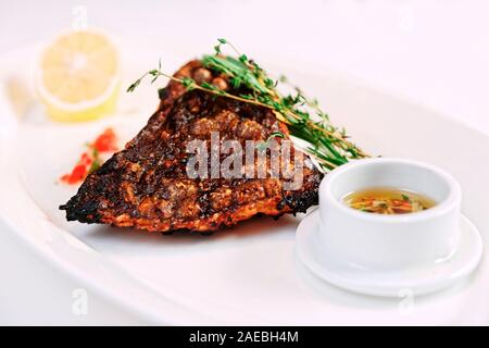 Grilled flounder (sole fish) with lemon, herbs and savory sauce, toned image - Stock Photo