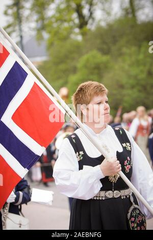 Oslo, Norway - May 17, 2010: National day in Norway. Norwegian woman in the national costume at traditional celebration and parade on Karl Johans Gate - Stock Photo