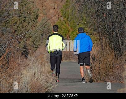 Runners jog along a riverside trail in early winter in Bend, Oregon - Stock Photo