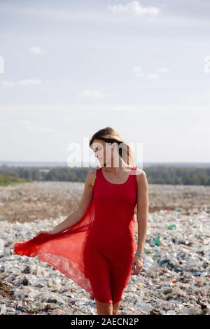 Nature pollution activist at a huge trash dump outdoors - Young blonde woman in a red dress - Looking at all the human waste and plastic in our world - Stock Photo