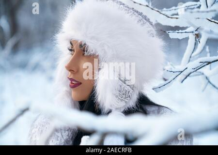 Close up of girl in warm winter hat on background of winter forest. Beautiful model in stylish clothing with perfect make up, plump lips near branches of trees covering snow looking away. - Stock Photo