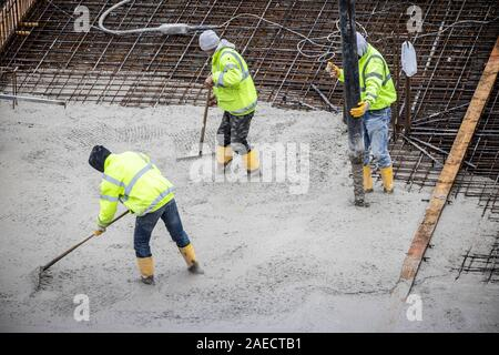 Construction site, concreting, the foundation of a building is concreted, the concrete is pumped onto the iron steel concrete mats, - Stock Photo
