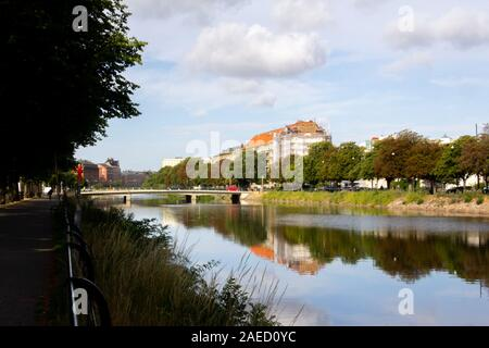 The trees and the buildings are making reflections in the canals of Malmö, Sweden, on a warm summer morning
