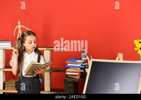 Back to school and education concept. Kid and school supplies on red wall background. Girl reads textbook near blackboard, copy space. Schoolgirl with interested face near bookshelf with school items - Stock Photo