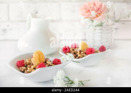 Organic muesli with raspberries for Breakfast in a white porcelain Cup with small white flowers on a light background. - Stock Photo