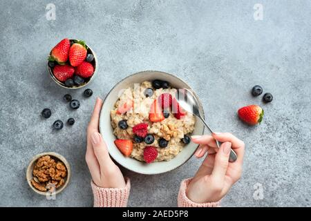 Oatmeal porridge bowl with berries in female hands on concrete background. Top view, copy space. Healthy vegan vegetarian diet, clean eating concept - Stock Photo