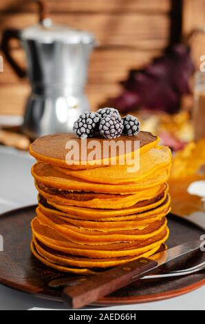 A heap of pumpkin pancakes with blackberries. Delicious breakfast. Vertical - Stock Photo