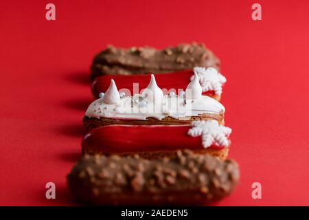 Red glazed eclair with white snowflakes on red colored background. Close up, minimalist food photography concept. Christmas dessert - Stock Photo