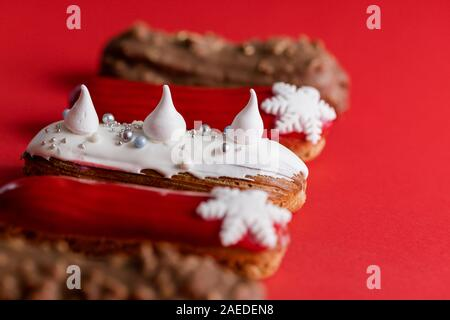 Red glazed eclair with white snowflakes on red colored background. Copyspace, close up, minimalist food photography concept. Christmas dessert - Stock Photo