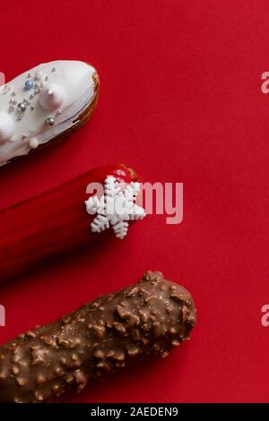 Red glazed eclair with white snowflakes on red colored background. Copyspace, flatlay, overhead, minimalism food photography concept. Christmas desser - Stock Photo