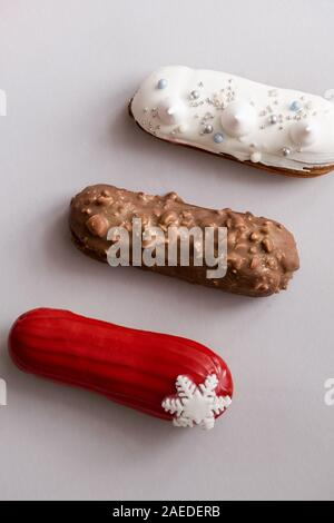 Red glazed eclair with white snowflakes on gray colored background. Flatlay, overhead, minimalist food photography concept. Christmas dessert - Stock Photo