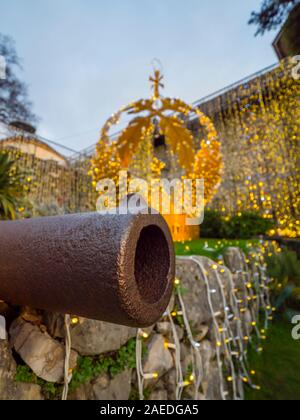 Isolated cannon muzzle tip golden crown in background Trsat fort in Rijeka in Croatia - festive illumination - Stock Photo