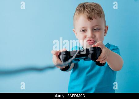 Little kid boy 2-3 years old wearing blue clothes hold in hand joystick for gameson blue background children studio portrait. People childhood - Stock Photo