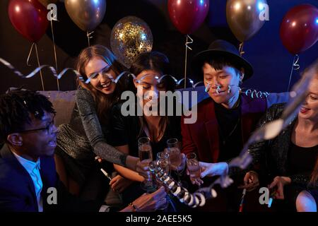High angle view at multi-ethnic group of trendy young people clinking champagne glasses during party in nightclub - Stock Photo