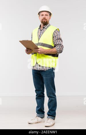 Bearded young engineer with clipboard standing in front of camera in isolation - Stock Photo