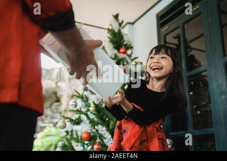 beautiful daughter giving her father a present on christmas day celebration - Stock Photo
