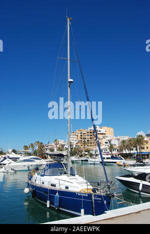 Luxury yachts and boats moored in the harbour with apartments and restaurants to the rear, Cabopino, Marbella, Spain. - Stock Photo