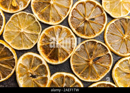 Slices of dried lemons and limes lying on dark table - Stock Photo