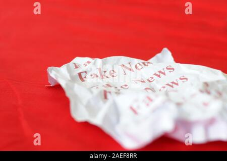 Fake news written in white paper lying against color background with copy space in the right side - Stock Photo