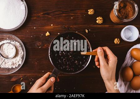 Female's hands mix melted chocolate with nuts and dried cherries in saucepan among ingredients for baking delicious homemade brownie cake, top view. - Stock Photo