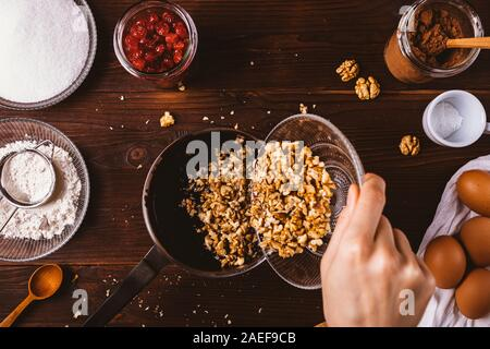 Top view female's hand adding chopped walnuts into melted dark chocolate in saucepan among ingredients for baking brownie cake on rustic background. - Stock Photo
