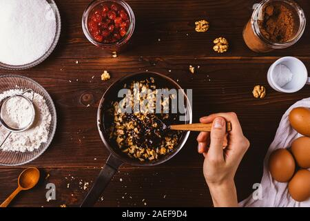 Top view process of making dough for homemade brownie cake. Woman's hand mix melted chocolate with chopped nuts in saucepan among other ingredients on - Stock Photo