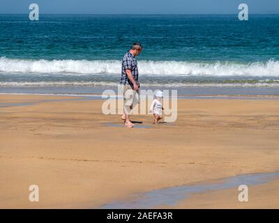 Adult male and toddler (possibly father and son) taking first steps on sunny, sandy Scottish beach with waves and sea beyond Scotland, UK - Stock Photo