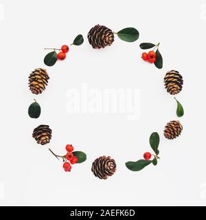 Beautiful eco friendly Christmas wreath made of pine cones and cotoneaster branches on white wooden background. Space for text. Creative flat lay. Zer - Stock Photo