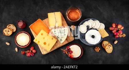 Cheese board panorama with wine and fruit, a flat lay, shot from the top on a black background - Stock Photo