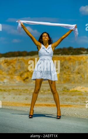 Teen girl serious closed eyes spread spreading legs hands arms holding White scarf - Stock Photo