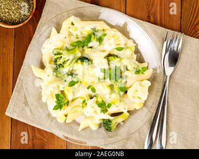 Broccoli pasta in glass plate on a dark brown wooden table, top view - Stock Photo