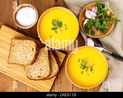Two brown bowl of pumpkin soup with parsley and pumpkin seeds on a brown dark wooden background, top view - Stock Photo