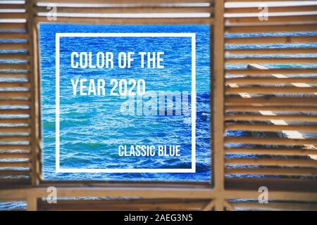 A square window overlooking classic blue colores sea from a wooden house with cracks. Traveling in nature. - Stock Photo