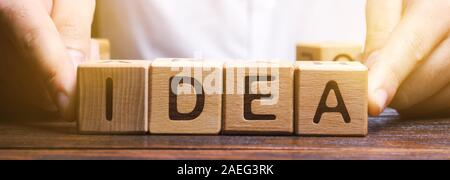 Businessman puts wooden blocks with the word Idea. Generation of innovative business ideas. Creative process. Innovation and solution. Inspiration Stock Photo