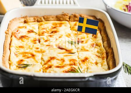 Swedish traditional cheese pie in black oven dish, gray background. Swedish cuisine concept. - Stock Photo