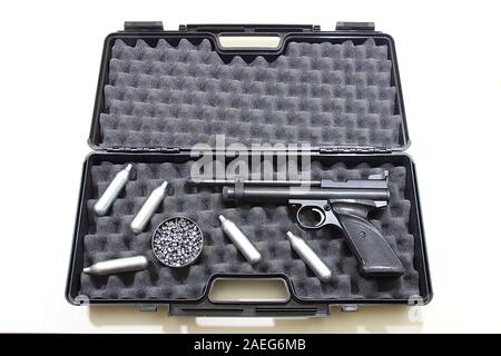 Air gun pistol in a plastic hard pistol case with round box of lead pellets and capsules of 12 grams CO2 gas. Top view, isolated on white background - Stock Photo