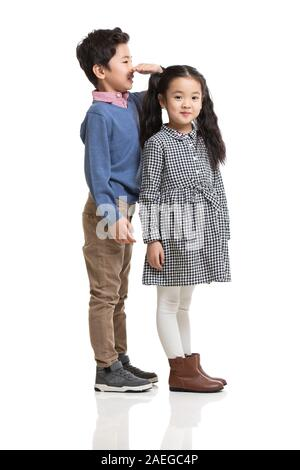 Two children measuring height - Stock Photo