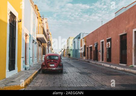 Old red Volkswagen Beetle parked on one of the colorful streets of the colonial town of Campeche, Mexico. - Stock Photo