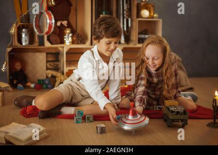 Happy holidays concept. Two kids playing with blocks on the floor, a creative Christmas tree made from wooden boxes decorated by garland and children toys on the background. Young girl and boy in vintage stylish clothes having fun playing games, sitting on the floor. New Year's party. Unique vintage interior. - Stock Photo