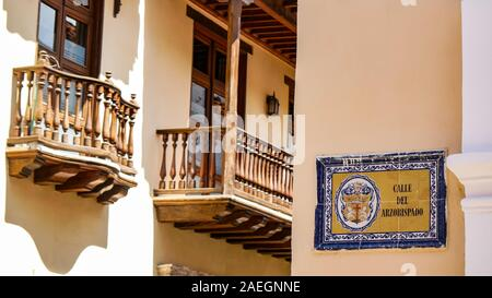Colonial house balconies and cute Street name sign made by tile on the streets of Cartagena de Indias. Name of the street: Calle del azorbispado - Stock Photo
