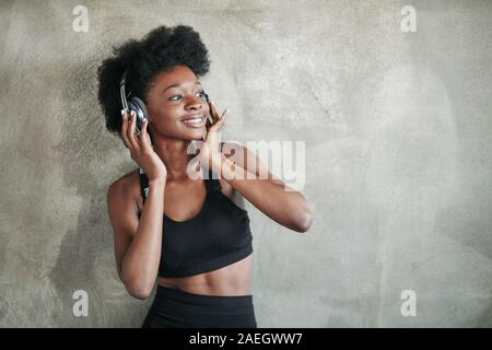 Good body shape. Portrait of african american girl in fitness clothes having a break after workout - Stock Photo