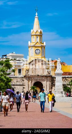Locals walking in front of the clock tower gate which is  the main entrance into the old city of Cartagena