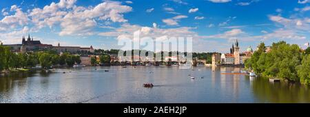 The city of Prague, Czech Republic with the Charles Bridge over the Vltava River on a bright and sunny day - Stock Photo